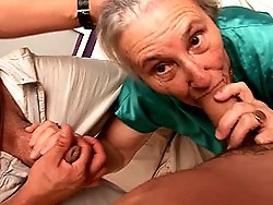 A sexy older granny sucks off two young guys at once
